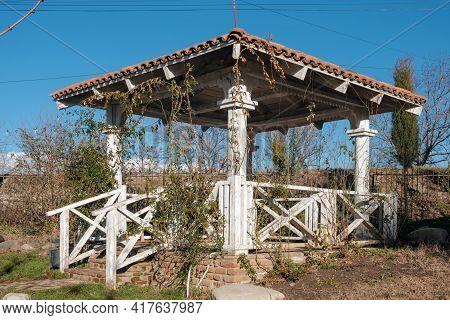 White Wooden Gazebo In The Garden Overgrown With Plants On The Blue Sky Background