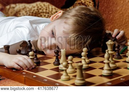 Pieces On A Chessboard.the Boy Chess Player Is Tired Of Training, Puts His Head On The Board And Res