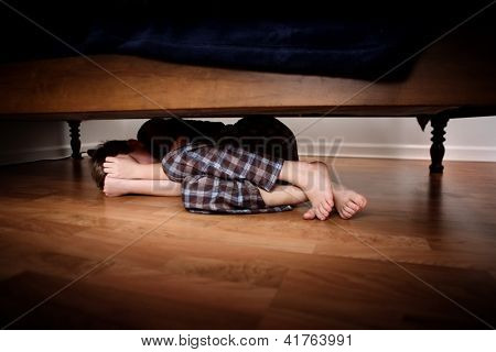 Fearful boy hiding under the bed