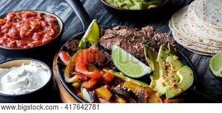 Narrow View Of A Skillet Filled With Ingredients To Make Fajitas Surrounded By Toppings And Tortilla