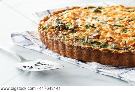 Close Up View Of A Freshly Baked Quiche On A Kitchen Towel Ready For Serving.