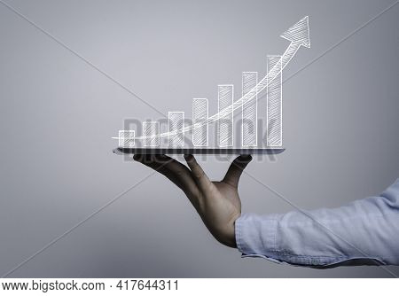 Trader Holding Computer Tablet With Hand Writing Of Chart And Graph With Increasing Arrow , Technolo