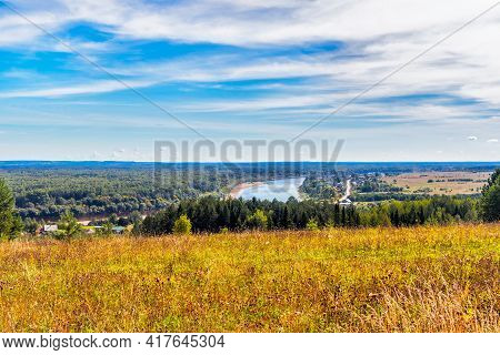 Rural Landscape With River And Woodland On The Horizon In Summer