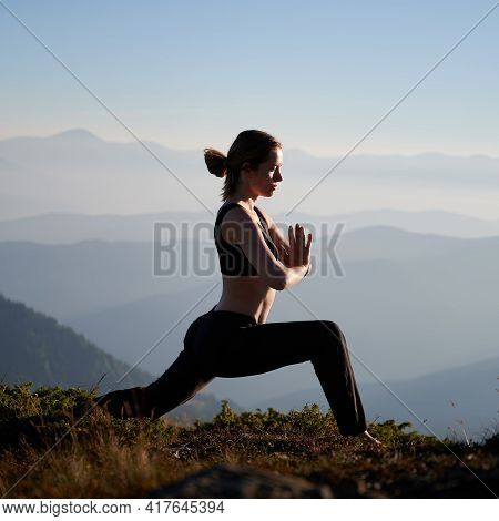 Fit Young Woman In Sportswear Doing Yoga Exercise Outdoors In Mountains. Female Person Doing Lunge A