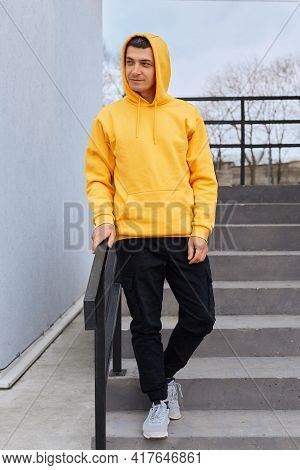 Attractive Brunette Guy Standing On Stairs In Open Air And Looking Dreamy Away, Young Man Dresses Ye