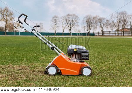 Mowing Or Cutting Long Grass With Lawn Mower. Gardening, Taking Care Of Sward. Side View Of Special