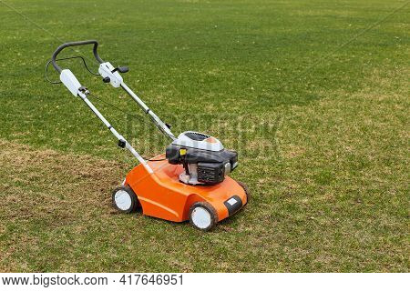 Lawn Mover On Green Grass On Background Of Field Or Garden. Machine For Cutting Lawns. Grass-cutter