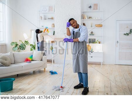 Full Length Of Young Black Guy Leaning On Mop, Feeling Tired Of Housecleaning With His Wife, Empty S