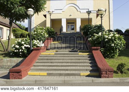 Steps To A Well Maintained Yellow Small Office Building With No Windows. No People. Blooming Bushes
