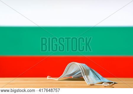 A Medical Mask Lies On The Table Against The Background Of The Flag Of Bulgaria. The Concept Of A Ma