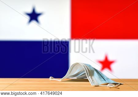 A Medical Mask Lies On The Table Against The Background Of The Flag Of Panama. The Concept Of A Mand