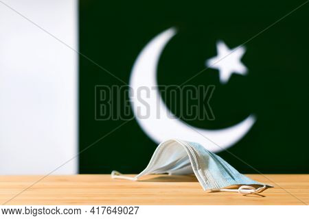 A Medical Mask Lies On The Table Against The Background Of The Flag Of Pakistan. The Concept Of A Ma