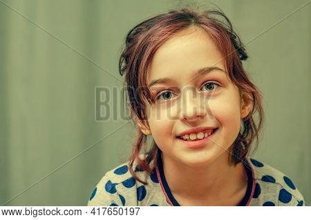 Young Girl In Pajamas. Girl In Pajamas. Girl 9 Years Old In A Gray Dress With Blue Polka Dots