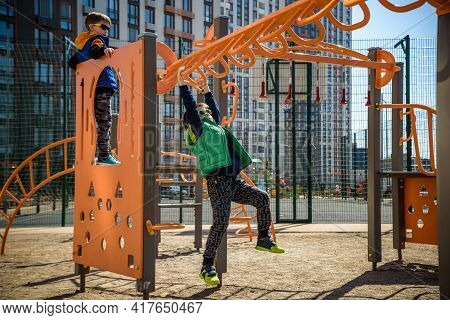 Active Little Child Playing Climbing Spring Metal At School Yard Playground. Kids Play And Climb Out