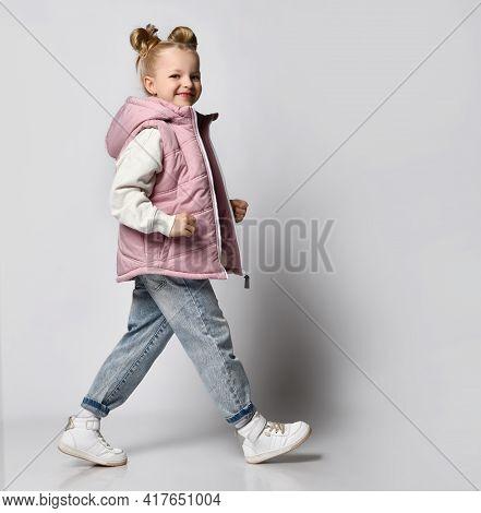 Studio Shot Of Little Girl In Warm Outwear Pink Sleeveless Vest, Jeans, Sneakers And Sweatshirt Walk
