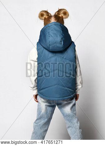 Studio Shot Of Little Girl In Warm Outwear Blue Sleeveless Vest With Hood, Jeans And Sweatshirt Stan