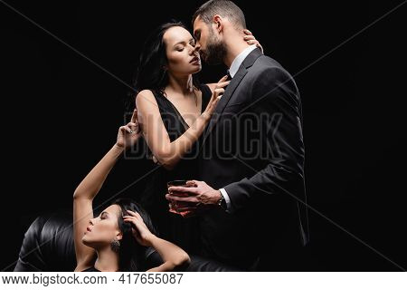 Passionate Woman Sitting Near Lovers Kissing Isolated On Black.