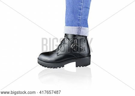 Leg In Blue Rolled Up Jeans And Black Lace-up Boot With Buckles And Straps. Isolated On White.