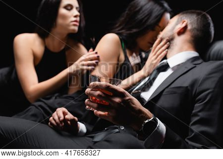 Man Holding Glass Of Whiskey Near Passionate Women Seducing Him Isolated On Black, Blurred Backgroun