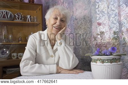 Old Lonely Happy Woman Sitting Near The Window In His House With Flowers