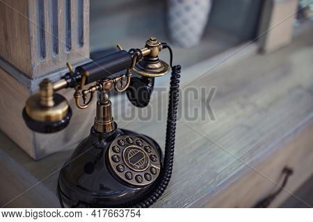 An old Fashioned rotary telephone sitting on a desk. This is a selective focus photo of a vintage piece of communication technology with copy space