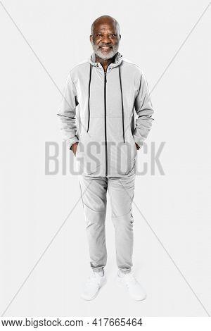Senior man in light gray tracksuit sportswear fashion portrait full body