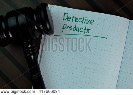 Defective Products Write On A Book Isolated On Wooden Table.