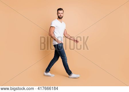 Full Length Photo Of Young Handsome Man Confident Serious Go Walk Step Hand In Pocket Isolated Over
