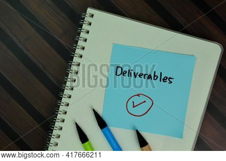 Deliverables Write On Sticky Notes Isolated On Wooden Table.