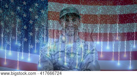 Composition of smiling american soldier with glowing fireworks over american flag. american patriotism, celebration and protection concept digitally generated image.