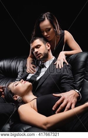 Man In Suit Sitting On Leather Couch Near Seductive Women Isolated On Black.