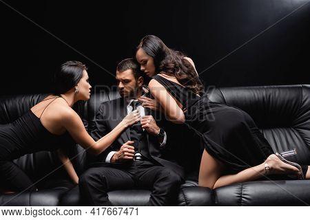Sexy, Elegant Women Seducing Businessman Sitting On Leather Couch On Black.