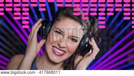 Composition on graphic music equalizer over portrait of smiling female dj holding headphones in club. entertainment, music and clubbing concept digitally generated image.