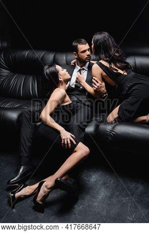 Passionate Women In Elegant Dresses Seducing Young Businessman Isolated On Black.