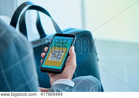 closeup of a young caucasian businessman, wearing an elegant gray suit, having a simulated electronic covid-19 immunity passport in his smartphone, sitting in the waiting hall of an airport
