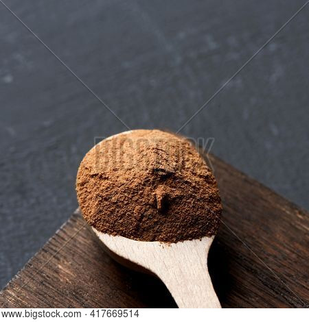 closeup of a wooden spoon full of camu-camu powder on a dark wooden tray, placed on a dark gray surface, in a square format