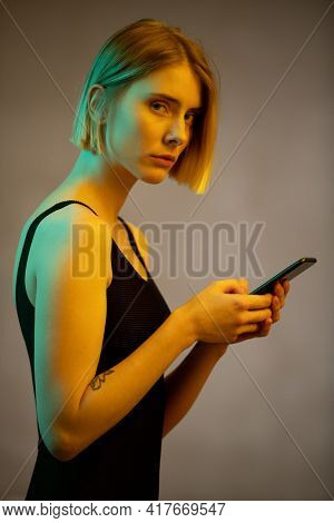 Portrait of young beautiful woman in black top looking at camera while using mobile phone isolated on grey background