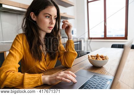 Brunette young woman sitting at the kitchen table with laptop computer
