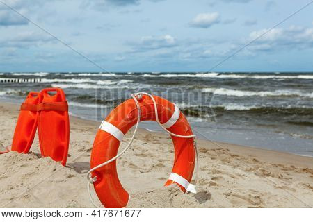 A red lifeguard stuck in the sand on the beach