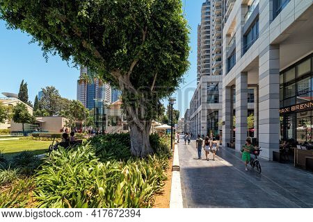 TEL AVIV, ISRAEL - JULY 18, 2018: People walking on boulevard at Sarona Park - modern, recently renovated urban area with outdoor restaurants and retail stores, popular place of leisure.