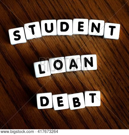 Student loan debt words letters on block dice representing massive payments and financial stress