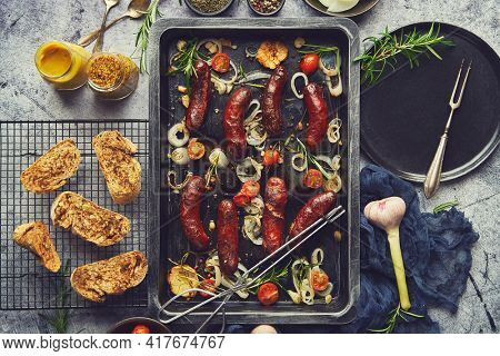 Delicious grilled sausages served on metal rusty tray. With barbecued vegetables