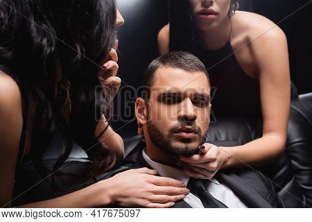 Sensual Women Seducing Young Businessman On Black Background.