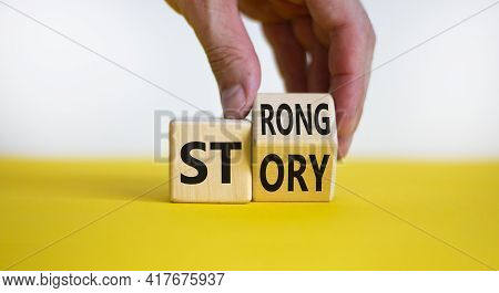 Strong Story Symbol. Businessman Turns Wooden Cubes With Words 'strong Story'. Beautiful Yellow Tabl