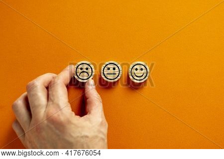 Quality And Feedback Symbol. Various Emoticons Made Of Wooden Circles. Beautiful Orange Background.