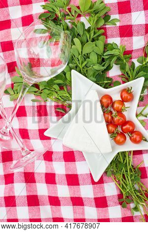 Glasses, Bread And Cheese On A Red Tablecloth