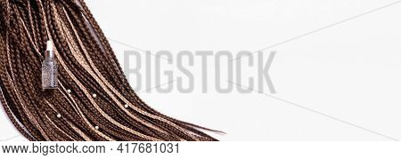 Banner. Thin Brown African Braids And A Jar Of Care Oil On A White Background. Hair Close-up, Braide