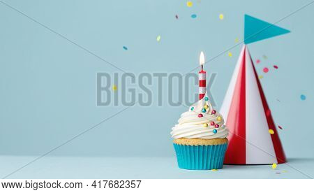 Birthday cupcake with one birthday candle and red and white striped party hat