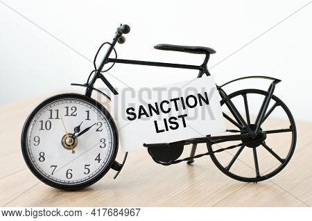Sanction List Inscription On A White Business Card Next To The Clock On A Light Background