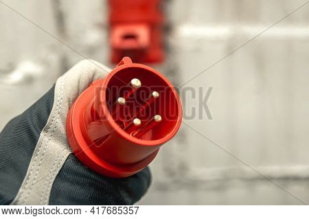 High Voltage Plug In Hand. Connecting A 380 Volt High Voltage, Three Phase Plug To An Outlet.